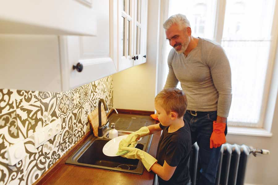 Child doing dishes while dad helps