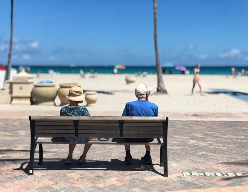 Man and lady sitting on bench at the beach