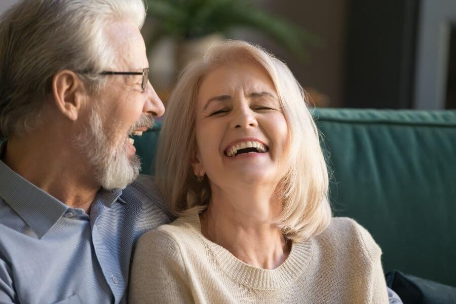 Man and woman laughing on the couch