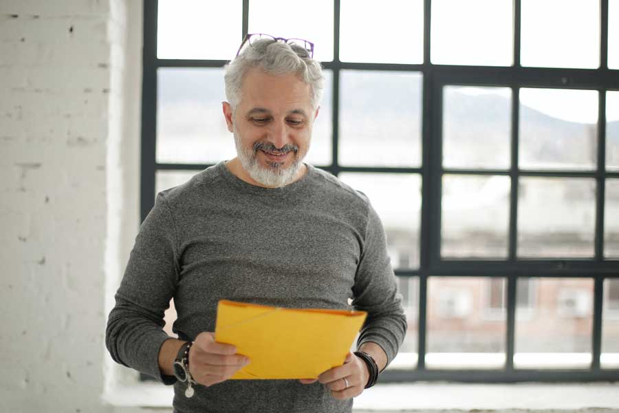 Man in grey shirt looking at papers and smiling