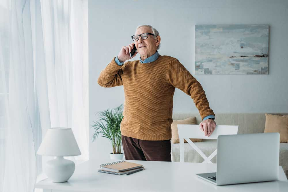 Old man on a cell phone in brown sweater