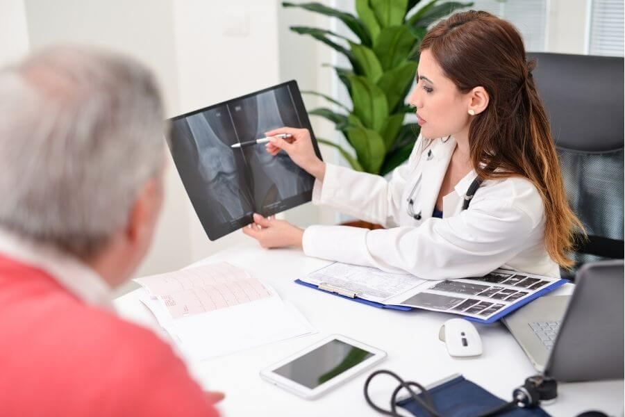 doctor showing joint scans to senior man