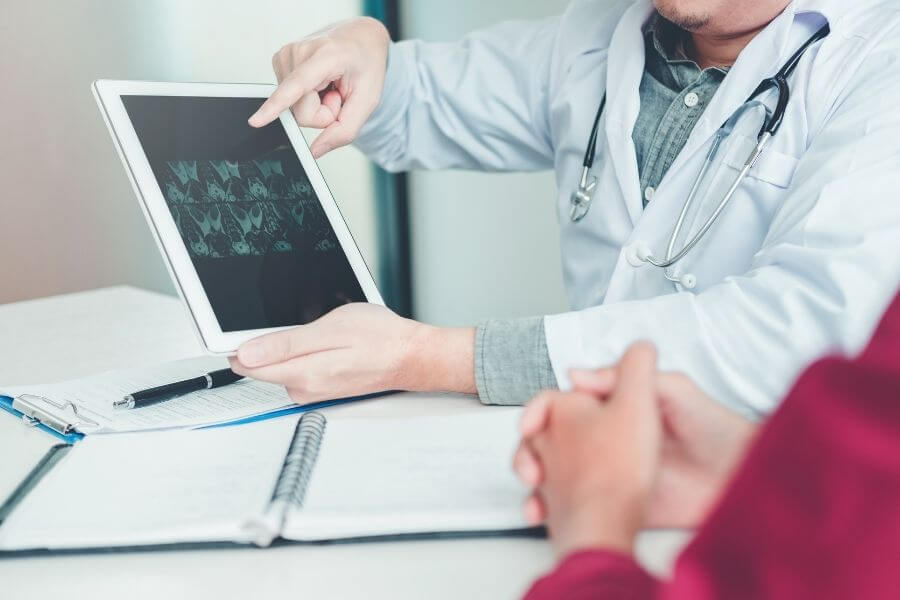 doctor explaining lung scans on computer