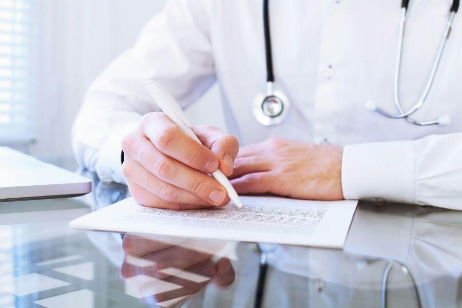 doctor writing on paper with pen