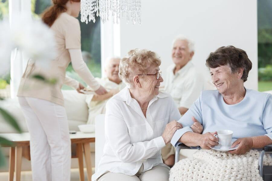 two elderly ladies smiling at each other