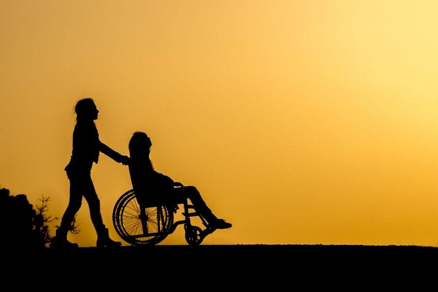 silhouette of person pushing someone in wheelchair