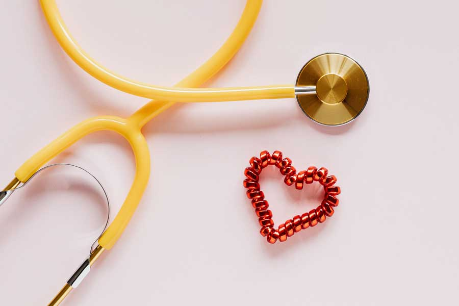 pink heart and stethoscope sitting next to each other