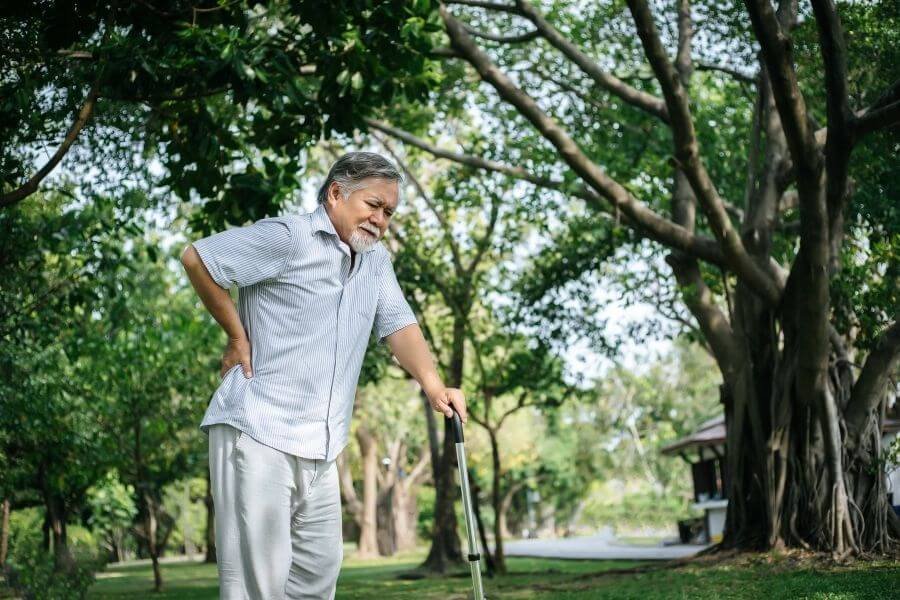 senior man in park with cane in pain