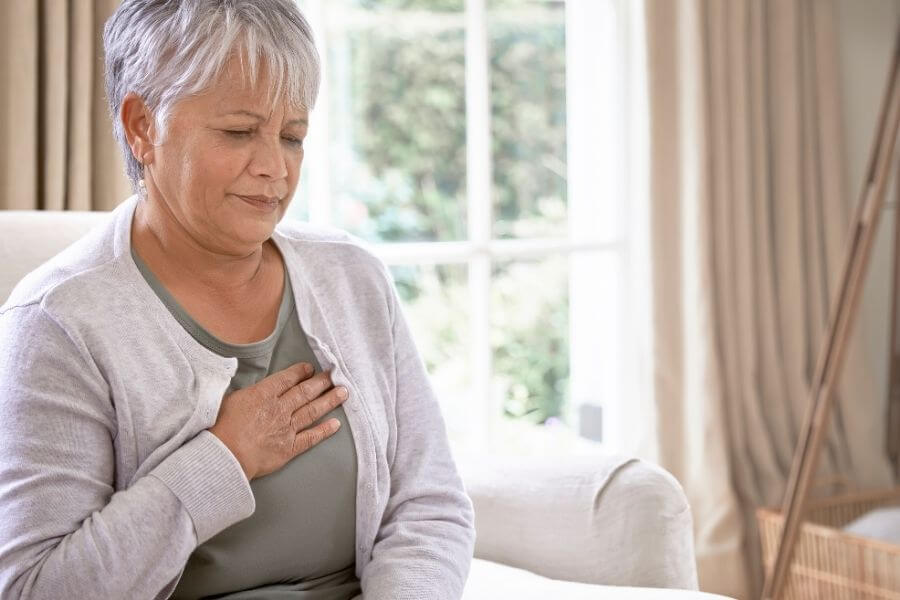senior woman sitting on couch holding chest