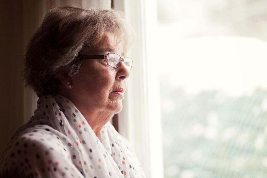 woman in glasses and shirt looking out the window