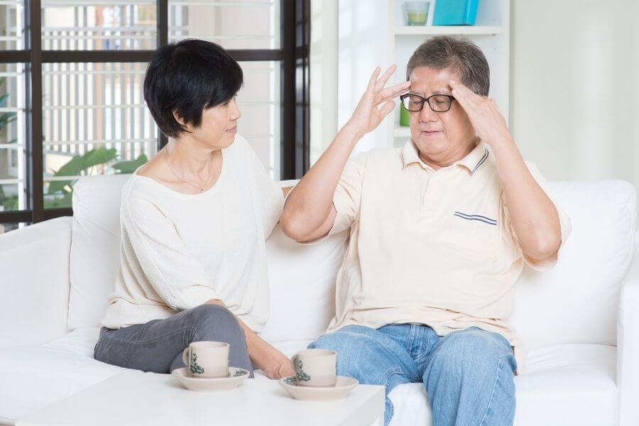 elderly couple sitting on couch man holding head