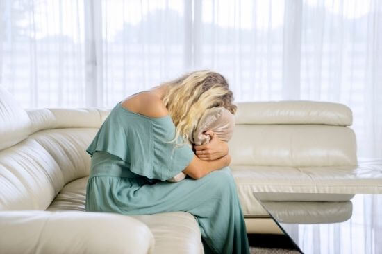 blonde girl on couch crying into pillow