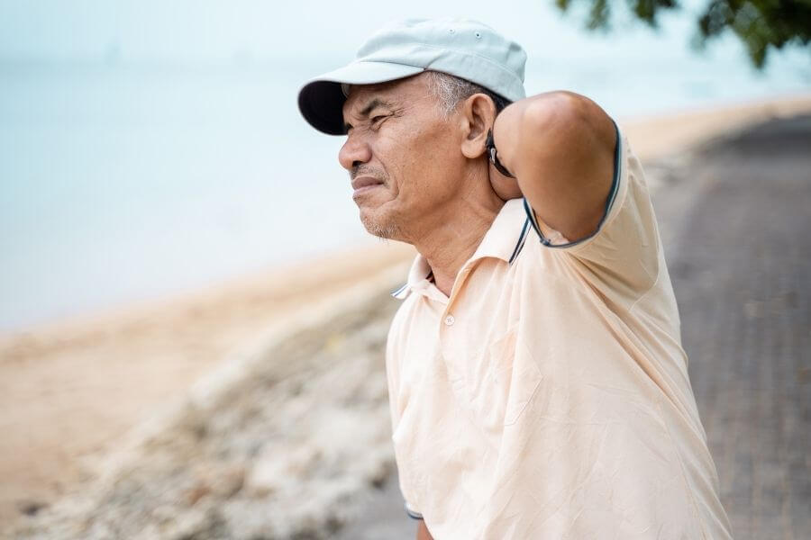 old man in pain on beach holding neck