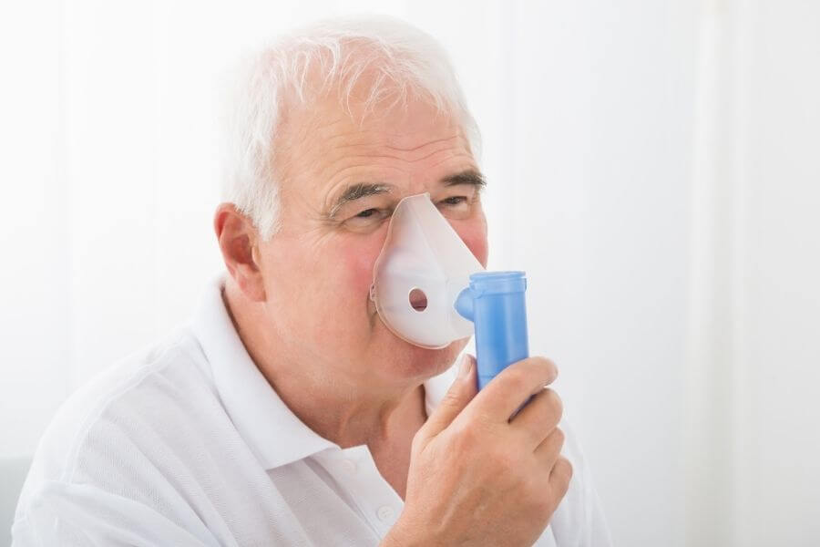 senior man using oxygen therapy mask