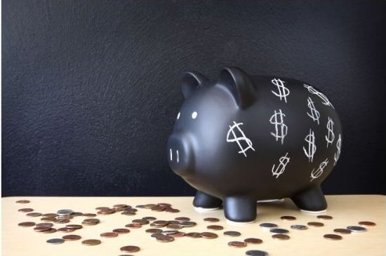 Black Piggy bank with coins on table
