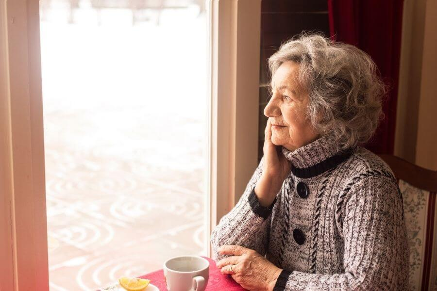 senior woman with tea looking out window