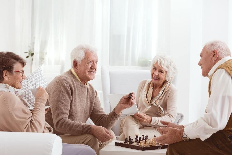 two happy senior couples paying chess