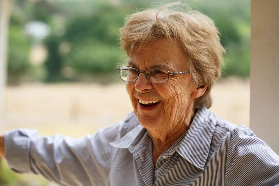 happy senior woman with glasses in blue