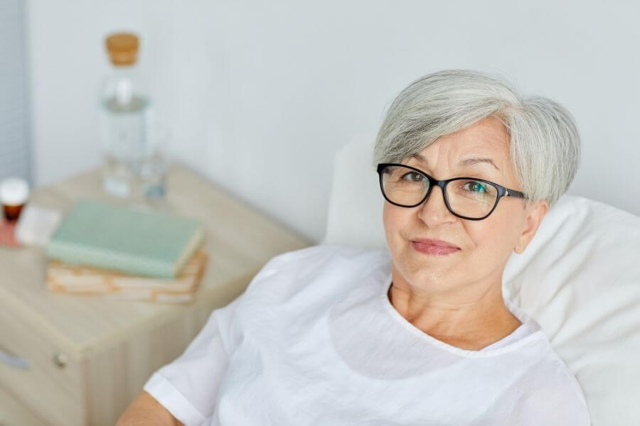 seniors woman with glasses in hospital bed