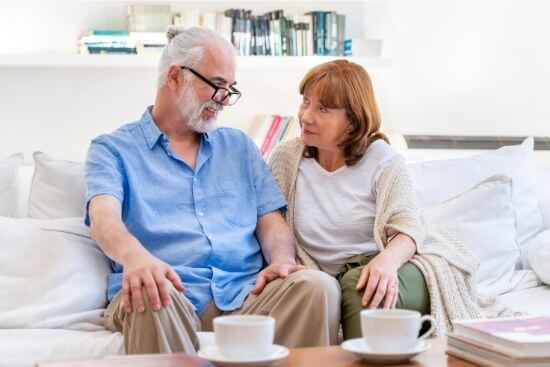 elderly couple on couch smiling at each other