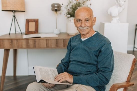 bald senior man sitting in living room reading