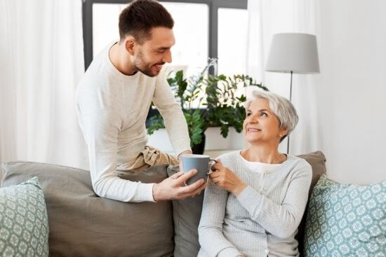 son giving mother on couch coffee mug