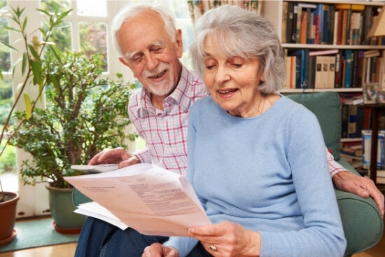 elderly couple reviewing papers