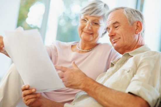 senior couple on couch looking at paperwork
