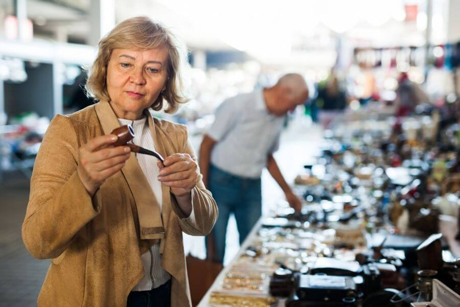 woman buying tobacco pipe at market