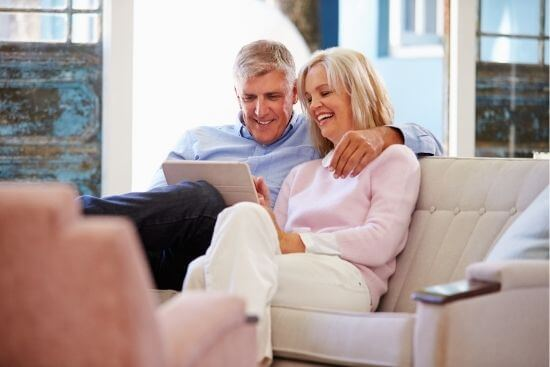 Man and woman on couch and ipad