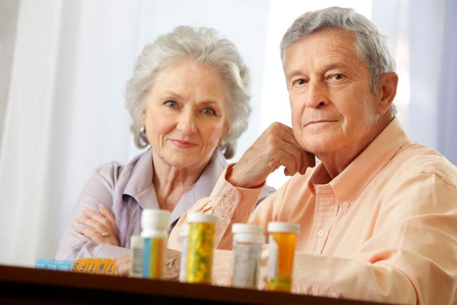 elderly couple with rx bottles on table