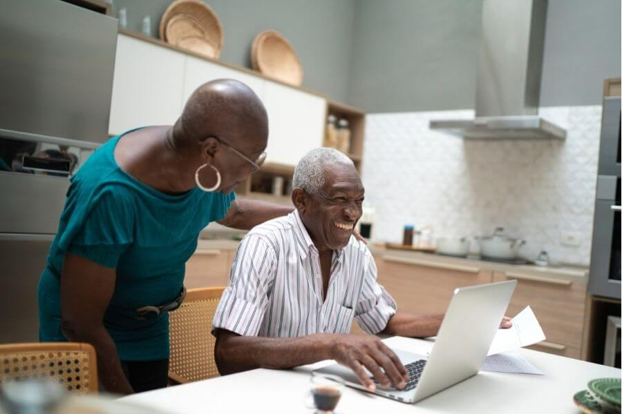 smiling elderly couple on computer