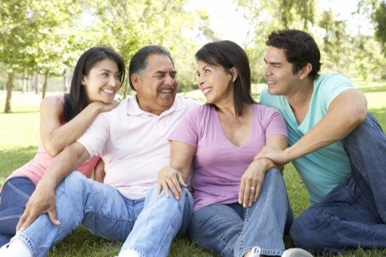 smiling family sitting on grass