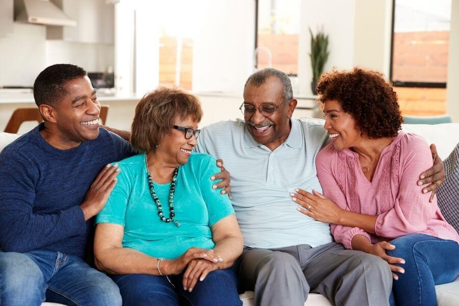four adults sitting on couch smiling
