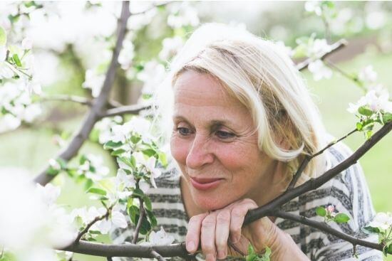 woman leaning on a tree branch smiling