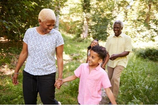 family walking in woods with elderly couple