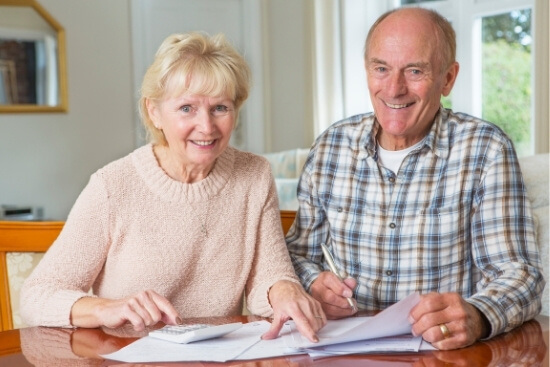 couple at table with paperwork smiling