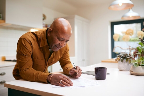 man filling out paperwork leaning on counter